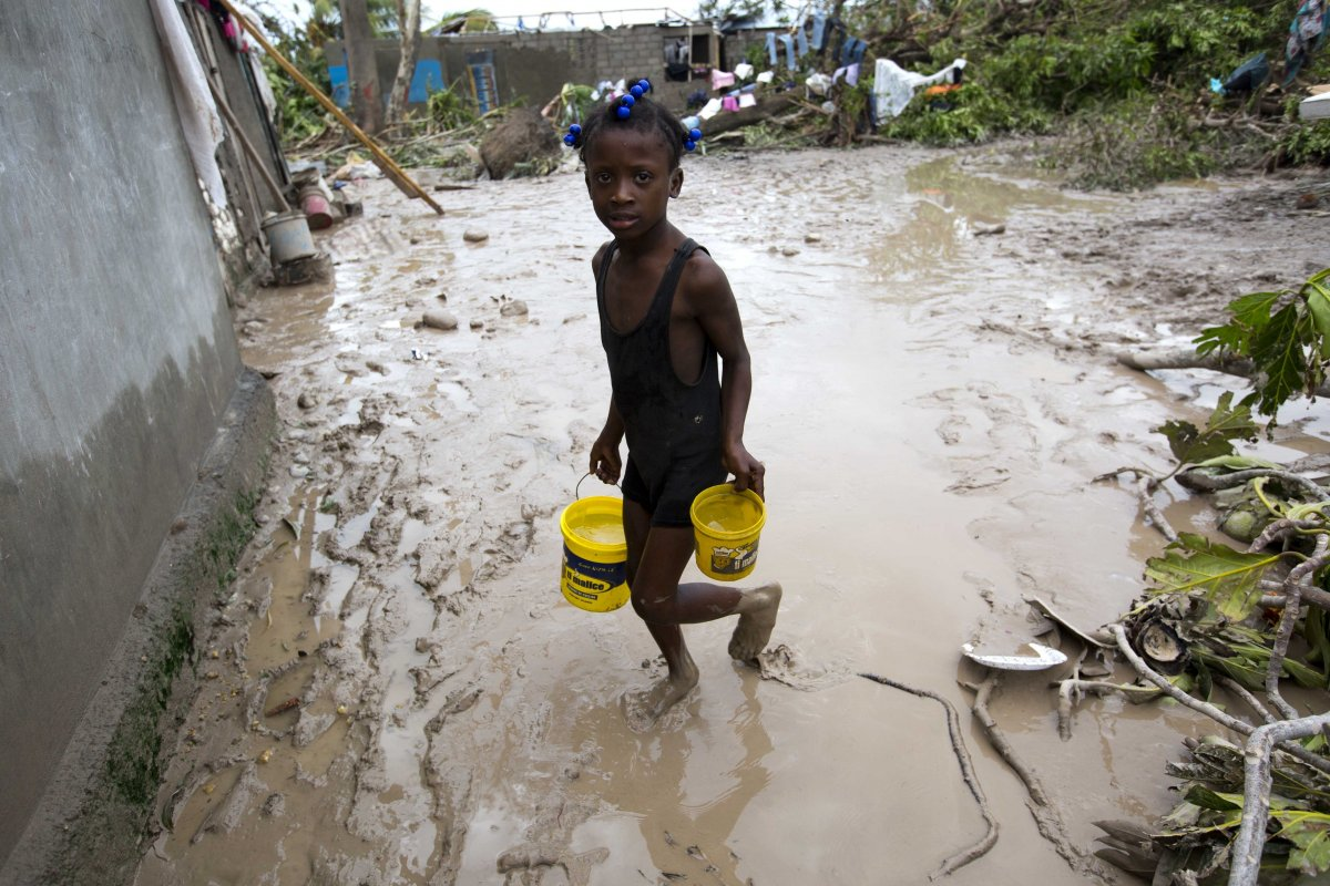 a-girl-lugs-buckets-of-drinking-water-in-the-aftermath-of-hurricane-matthew-in-les-cayes